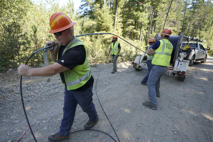 FILE - In this Wednesday, Aug. 4, 2021, file photo, Carl Roath, left, a worker with the Mason County (Wash.) Public Utility District, pulls fiber optic cable off of a spool, as he works with a team to install broadband internet service to homes in a rural area surrounding Lake Christine near Belfair, Wash. (AP Photo/Ted S. Warren, File)