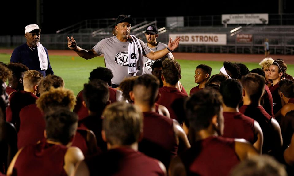 Head Coach Willis May speaks with members of the Marjory Stoneman Douglas High School football team as they started their first practice for a new season just after midnight on Monday, July 30, 2018, in Parkland, Fla. The players, their school, and community still grieves for the 17 lives lost at the school on Feb. 14. (AP Photo/Joe Skipper)