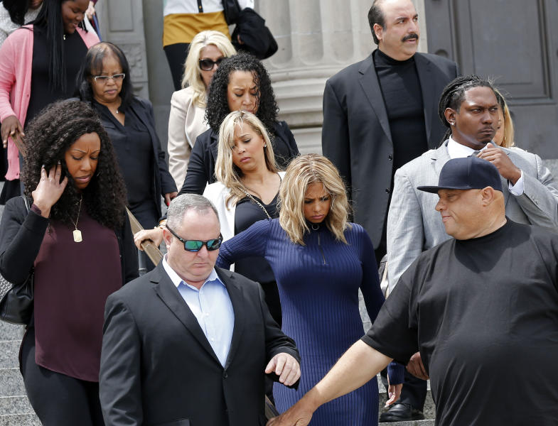 Racquel Smith, center front, widow of former New Orleans Saints star Will Smith, leaves the Orleans Parish criminal courthouse with supporters, during a recess for a sentencing hearing for Cardell Hayes, who killed her husband and shot her, and was convicted of manslaughter in New Orleans, Wednesday, April 19, 2017. (AP Photo/Gerald Herbert)