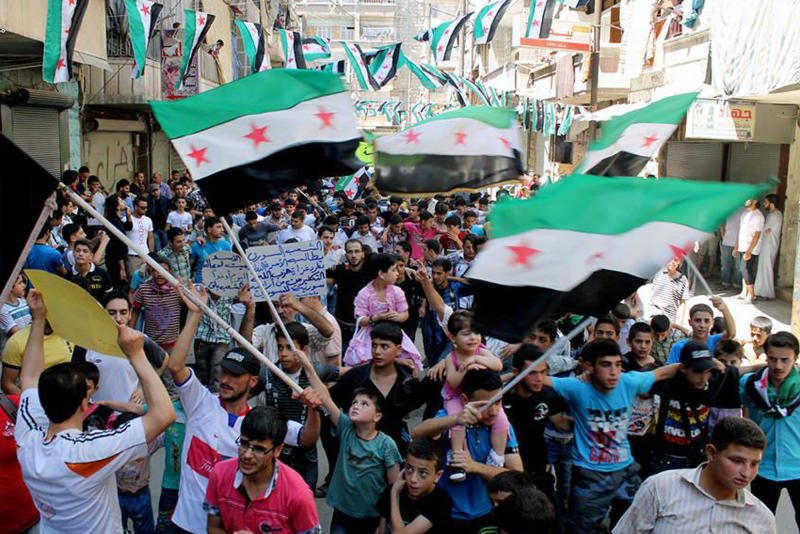This citizen journalism image provided by Aleppo Media Center AMC which has been authenticated based on its contents and other AP reporting, shows anti-Syrian regime protesters holding Syrian revolution flags, during a demonstration in the neighborhood of Bustan Al-Qasr in Aleppo, Syria, Friday, June 28, 2013. Intense shelling by Syrian government troops on a village in the country's south killed several women and girls overnight as forces loyal to President Bashar Assad pushed ahead with an offensive against rebels near the border with Jordan, activists said Friday. (AP Photo/Aleppo Media Center AMC)