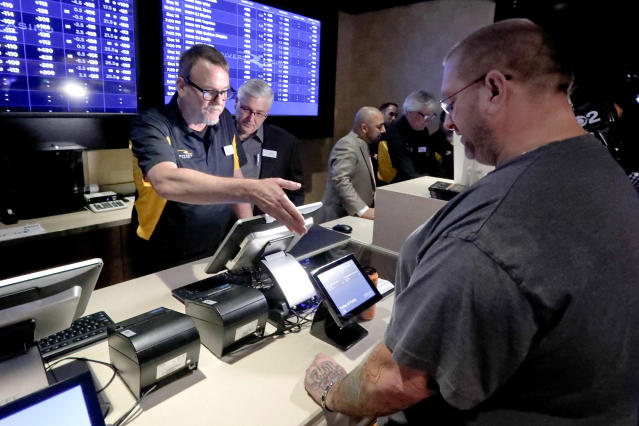 FILE - In this Dec. 13, 2018, file photo, Ryan Martin, right, looks over his wager at Rivers Casino, as the new, temporary sports betting area opened in Pittsburgh. Pending Pennsylvania Gaming Control Board approval, regular operations are scheduled to begin Saturday, Dec. 15. Marton made several wagers, including placing a $100 bet on the Pittsburgh Steelers to win the Super Bowl. Anyone willing to wager that the high-scoring Patriots or Rams will get shut out in the Super Bowl can count on a big payday if that unlikely scenario occurs. Prop bets aren't a big moneymaker for sports books during the season, but they pick up popularity as the nation is intensely focused on a single game. (AP Photo/Keith Srakocic. File)