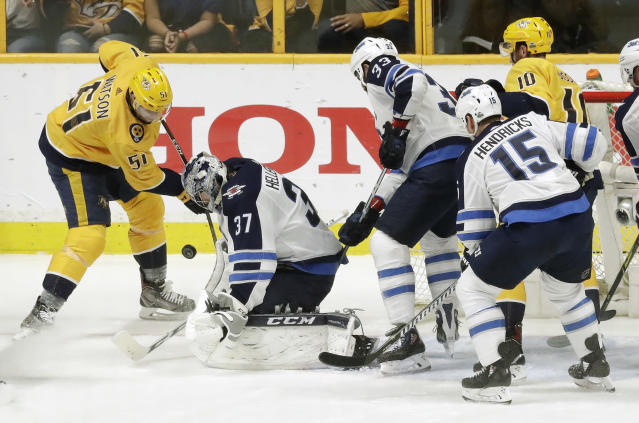 Winnipeg Jets goalie Connor Hellebuyck (37) blocks a shot by Nashville Predators left wing Austin Watson (51) during the first period in Game 2 of an NHL hockey second-round playoff series Sunday, April 29, 2018, in Nashville, Tenn. (AP Photo/Mark Humphrey)