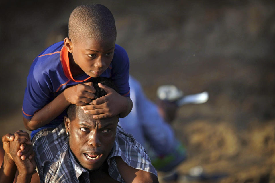 A man carries a boy across the Rio Grande river as migrants, many from Haiti, leave Del Rio, Texas to return to Ciudad Acuna, Mexico, early Wednesday, Sept. 22, 2021, some to avoid possible deportation from the U.S. and others to load up on supplies. (AP Photo/Fernando Llano)