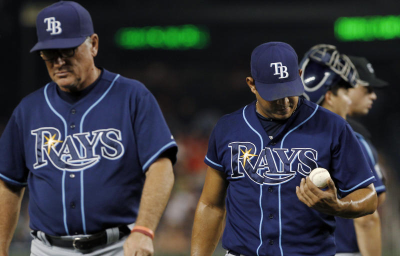 Tampa Bay Rays manager Joe Maddon, left, leads relief pitcher Joel Peralta from the baseball game during the eighth inning against the Washington Nationals at Nationals Park on Tuesday, June 19, 2012, in Washington. Peralta was ejected without throwing a pitch after the umpires found a foreign substance on his glove. The Rays won 5-4. (AP Photo/Alex Brandon)