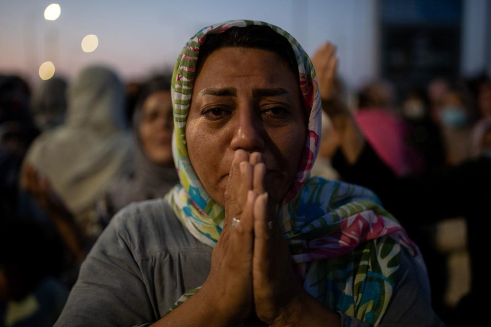 A woman reacts as refugees and migrants from the destroyed Moria camp pray near a new temporary camp where they will be accommodated, on the island of Lesbos, Greece, September 13, 2020. REUTERS/Alkis Konstantinidis