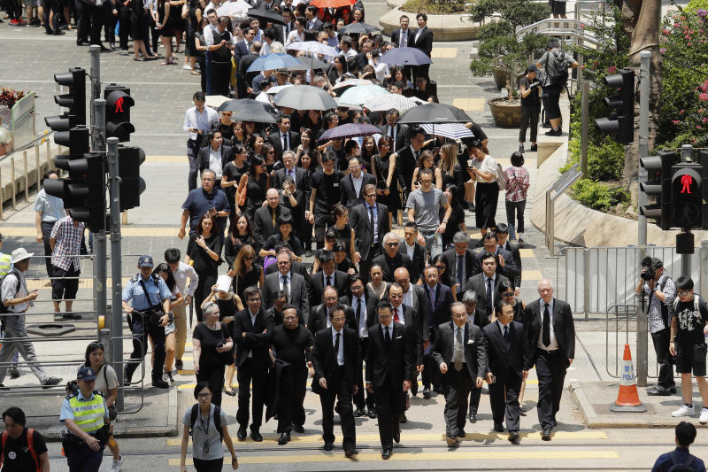 """Lawyers cross a street during a protest march in Hong Kong, Wednesday, Aug. 7, 2019. The head of Beijing's Cabinet office responsible for Hong Kong says the territory is facing its """"most severe situation"""" since the handover from British rule in 1997. (AP Photo/Kin Cheung)"""