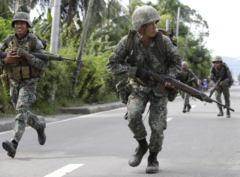 Philippine Marines cross an intersection to avoid a sniper fire during a standoff for the second day Tuesday Sept. 10, 2013 as about 200 Muslim rebels, enraged by a broken peace deal with the Philippine government, held scores of hostages as human shields at the southern port city of Zamboanga, in southern Philippines. More battle-ready troops and police were flown to the southern port city of Zamboanga in a bid to end the crisis. The troops have surrounded the Moro National Liberation Front guerrillas with their hostages in four coastal villages since the crisis erupted Monday. (AP Photo/Bullit Marquez)