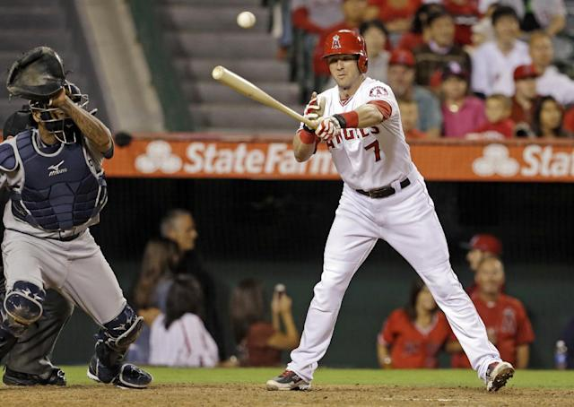 Los Angeles Angels' Andrew Romine misses for a strike as the ball sails over Seattle Mariners catcher Henry Blanco, allowing Collin Cowgill to steal home, in the seventh inning of a baseball game in Anaheim, Calif., Saturday, Sept. 21, 2013. (AP Photo/Reed Saxon)