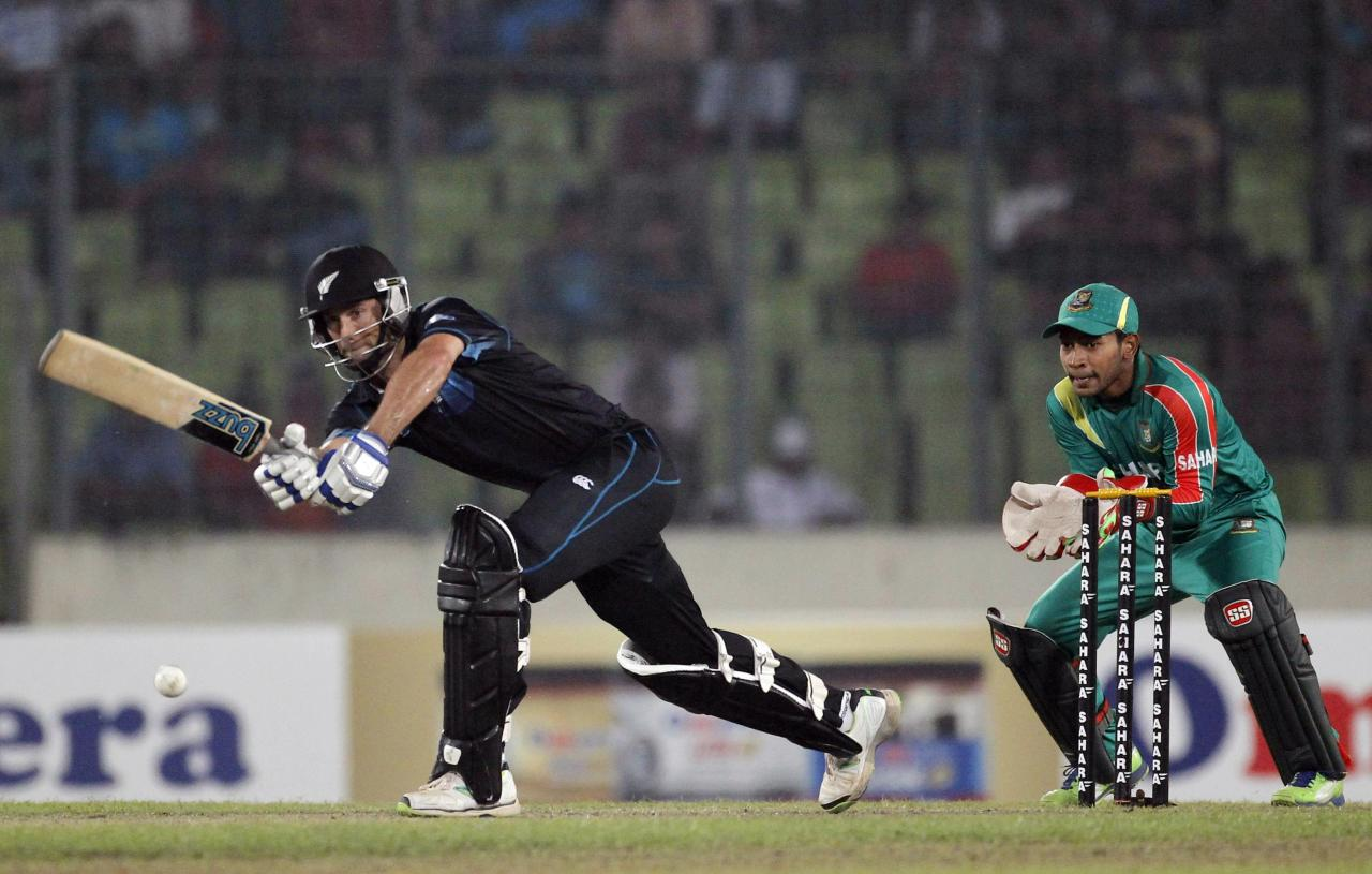 New Zealand's Grant Elliott plays a shot as Bangladesh's captain and wicket keeper Mushfiqur Rahim watches during their second one-day international (ODI) cricket match in Dhaka October 31, 2013. REUTERS/Andrew Biraj (BANGLADESH - Tags: SPORT CRICKET)