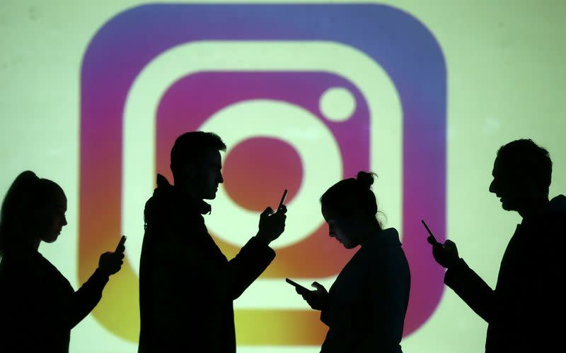 FILE PHOTO: Silhouettes of mobile users are seen next to a screen projection of the Instagram logo in this picture illustration