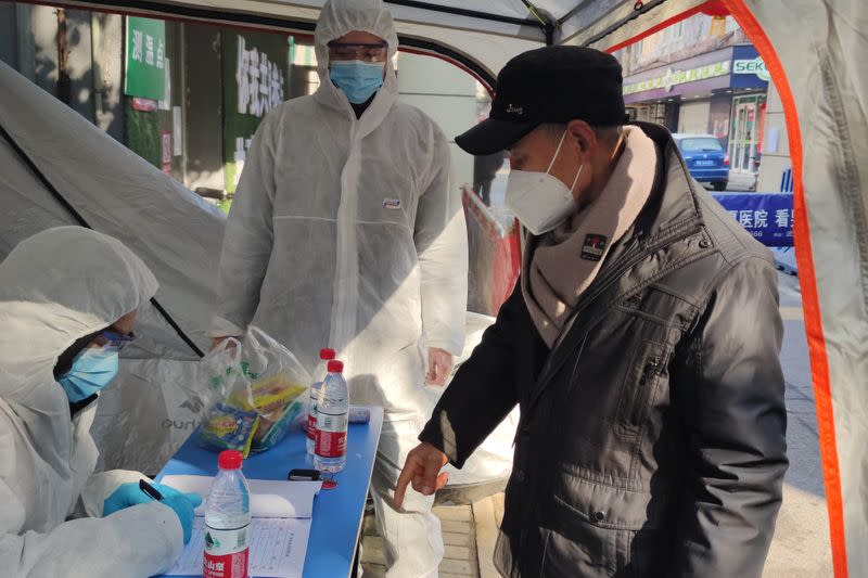 Volunteers in protective suits help a man with registration at a checkpoint of a residential compound, following the outbreak of the novel coronavirus in Wuhan