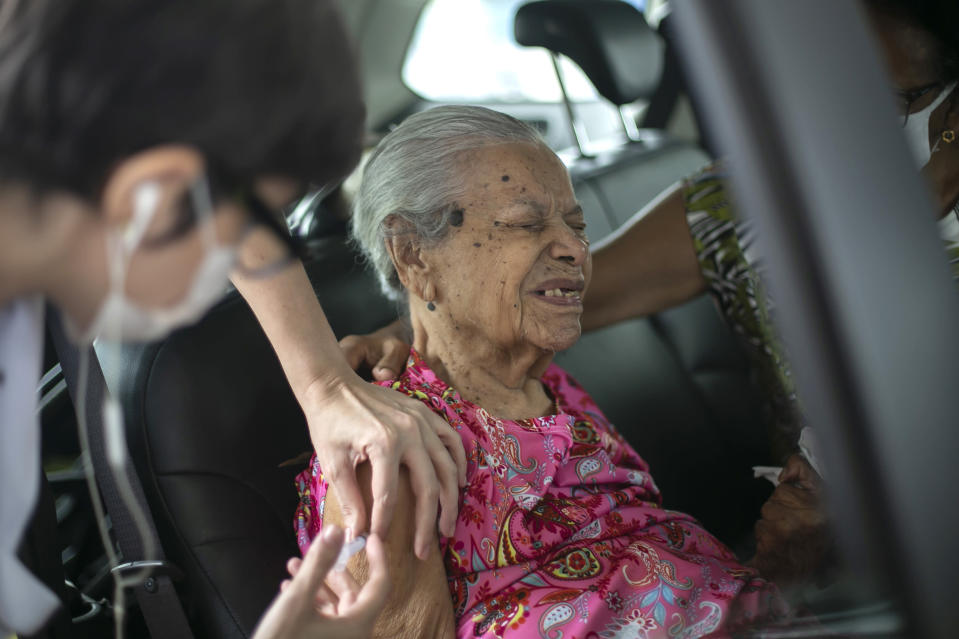 Maria de Lourdes, 101, grimaces as she receives a dose of the China's Sinovac Biotech COVID-19 vaccine at a drive-thru vaccination site in the Sambadrome, in Rio de Janeiro, Brazil, Saturday, Feb. 6, 2021. In a normal year, Rio's Sambadrome would be preparing for its great moment of the year: the famous Carnival parade. But a week before what should be the start of Carnival, the pandemic has replaced pageantry. (AP Photo/Bruna Prado)