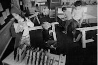 <p>Children work with saws in the wood shop of their elementary school. </p>