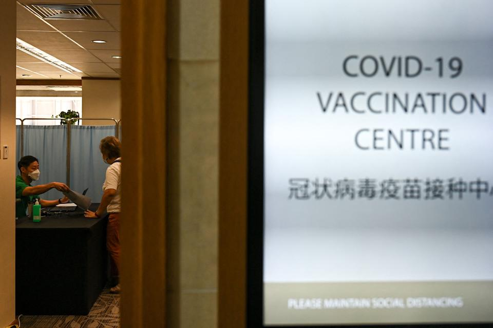A medical staff attends to a woman before receiving a dose of the Sinopharm Covid-19 coronavirus vaccine at the Mount Elizabeth hospital vaccine centre in Singapore.