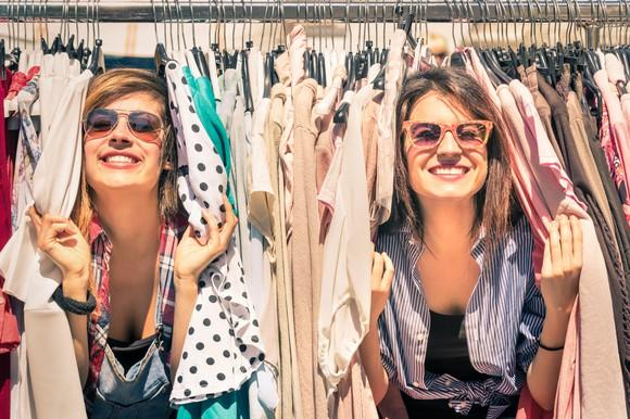 Two women hiding in racks of clothes.