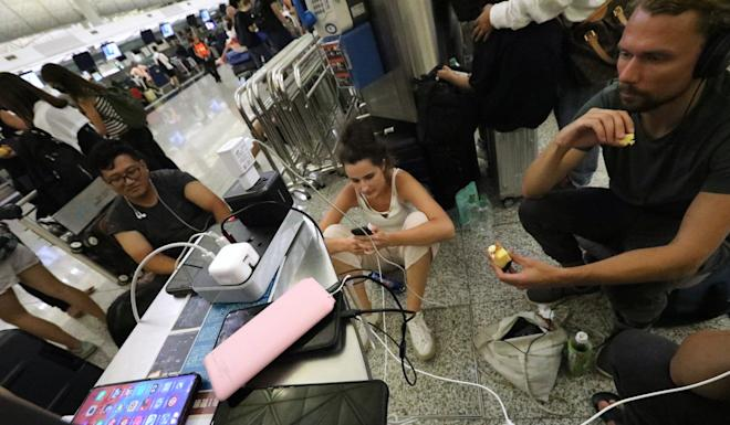 Stranded travellers charge their devices at Hong Kong International Airport on Tuesday. Photo: Felix Wong