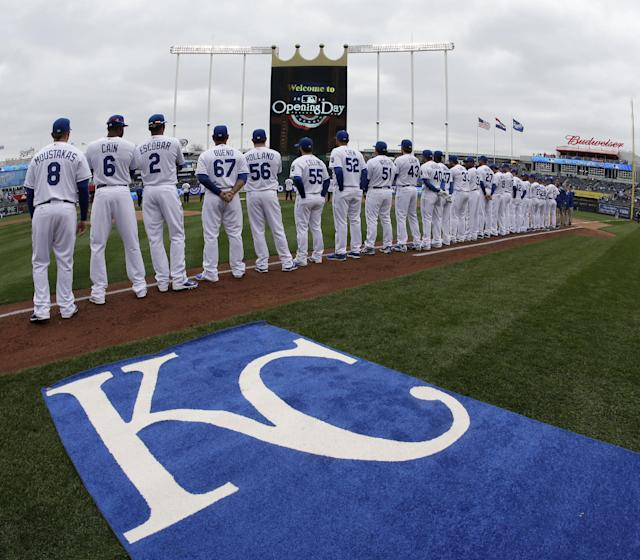 Players for the Kansas City Royals stand for the national anthem before a home opener baseball game against the Chicago White Sox Friday, April 4, 2014, in Kansas City, Mo. (AP Photo/Charlie Riedel)