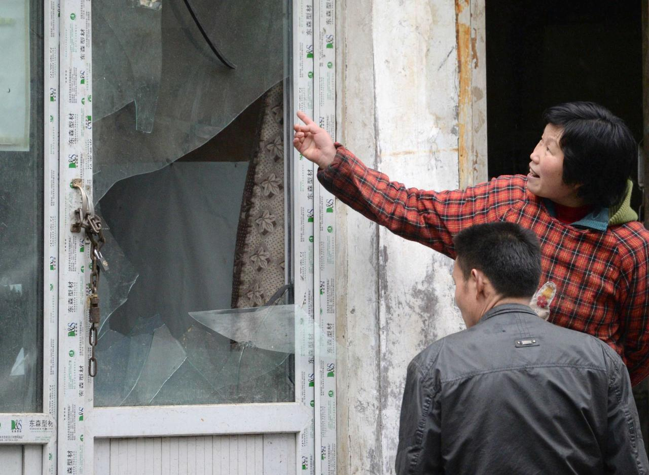 A woman points to a broken window at a building, which was damaged by an explosion in Urumqi on Thursday, in the Xinjiang Uighur Autonomous Region, in this photo taken by Kyodo on May 22, 2014. Five suicide bombers carried out the attack which killed 31 people in the capital of China's troubled Xinjiang region, state media reported a day after the deadliest terrorist attack to date in the region. Picture taken May 22, 2014. Mandatory credit REUTERS/Kyodo (CHINA - Tags: CRIME LAW CIVIL UNREST POLITICS) ATTENTION EDITORS - THIS IMAGE HAS BEEN SUPPLIED BY A THIRD PARTY. FOR EDITORIAL USE ONLY. NOT FOR SALE FOR MARKETING OR ADVERTISING CAMPAIGNS. MANDATORY CREDIT. JAPAN OUT. NO COMMERCIAL OR EDITORIAL SALES IN JAPAN. THIS PICTURE IS DISTRIBUTED EXACTLY AS RECEIVED BY REUTERS, AS A SERVICE TO CLIENTS. YES