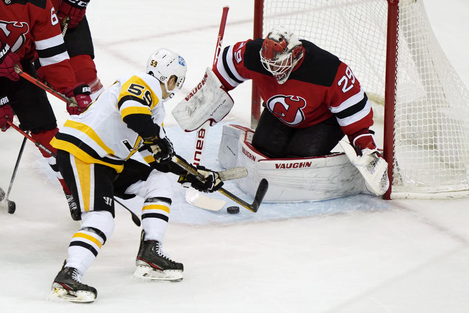 Pittsburgh Penguins left wing Jake Guentzel (59) tries to score in front of New Jersey Devils goaltender Mackenzie Blackwood (29) during the first period of an NHL hockey game, Sunday, April 11, 2021, in Newark, N.J. (AP Photo/Kathy Willens)