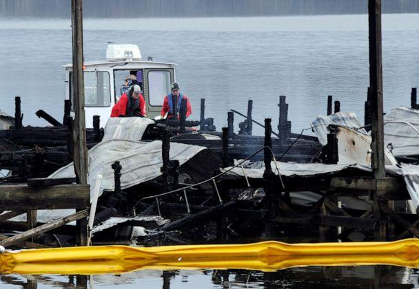 PHOTO: A crew looks at the charred remains of a boat following a fatal fire at a Tennessee River marina in Scottsboro, Ala., on Jan. 27, 2020. (Jay Reeves/AP)