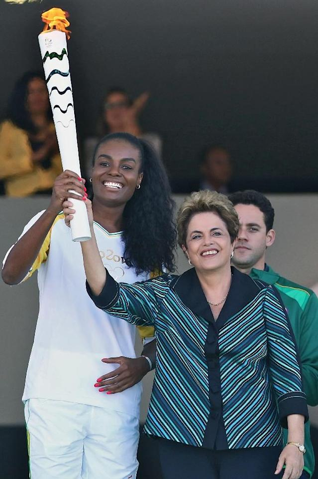 Dilma Rousseff (right) and Brazilian volleyball player Fabiana Claudino hold the Olympic torch at Planalto Palace in Brasilia in May (AFP Photo/Celio Messias)