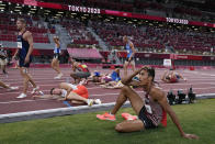 Competitors rest on the track following the decathlon 1500-meters at the 2020 Summer Olympics, Thursday, Aug. 5, 2021, in Tokyo. (AP Photo/David J. Phillip)