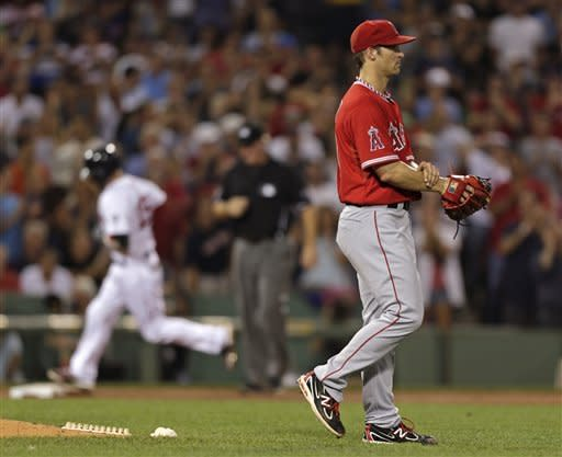 Los Angeles Angels pitcher C.J. Wilson walks off the mound as Boston Red Sox second baseman Dustin Pedroia (15) rounds the bases on his three-run home run in the second inning of a baseball game at Fenway Park in Boston, Thursday, Aug. 23, 2012. (AP Photo/Charles Krupa)