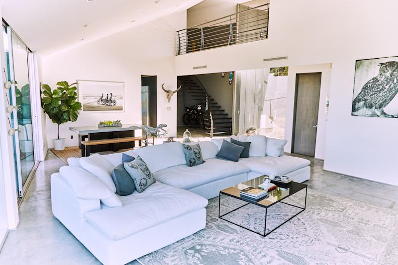 """Huston's attraction to RH's white Cloud sofa was instant. """"I went into the store on Melrose in L.A., sat on it, and I was like, 'Yeah, I definitely need this one."""" He brought the dining table from his previous home, as well as the owl painting that represents, to him, the era when he and his friends regularly skated all day and all night."""