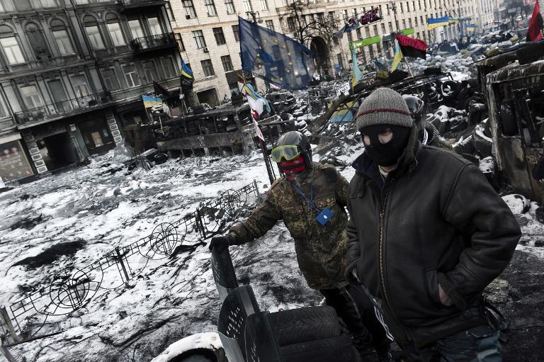 Anti-government protesters stand at a road block in Kiev on January 30, 2014