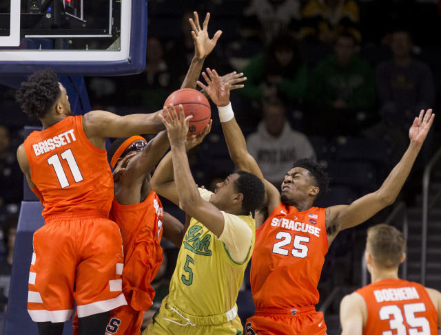 Notre Dame's D.J. Harvey (5) goes up for a shot with pressure from Syracuse's Oshae Brissett (11), Paschal Chukwu, and Tyus Battle (25) during the first half of an NCAA college basketball game Saturday, Jan. 5, 2019, in South Bend, Ind. Syracuse won 72-62. (AP Photo/Robert Franklin)