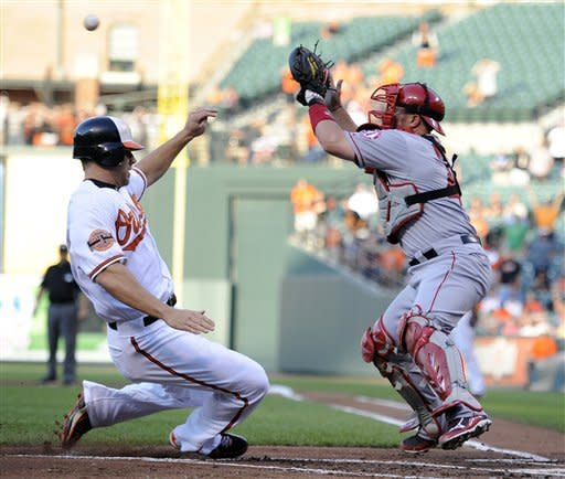 Baltimore Orioles' Chris Davis, left, begins his slide into home plate to score on a double by Adam Jones as Los Angeles Angels catcher Bobby Wilson, right, reaches for the ball during the first inning of a baseball game on Wednesday, June 27, 2012, in Baltimore. (AP Photo/Nick Wass)