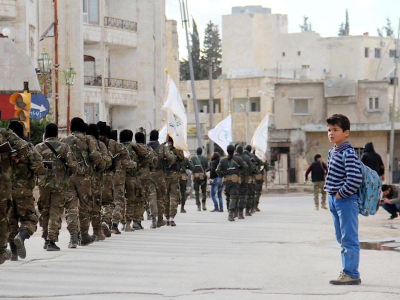 A Syrian boy looks at rebel fighters from the Jaish al-Fatah (or Army of Conquest) brigades, which include other rebel factions, marching in the city of Idlib (Getty)