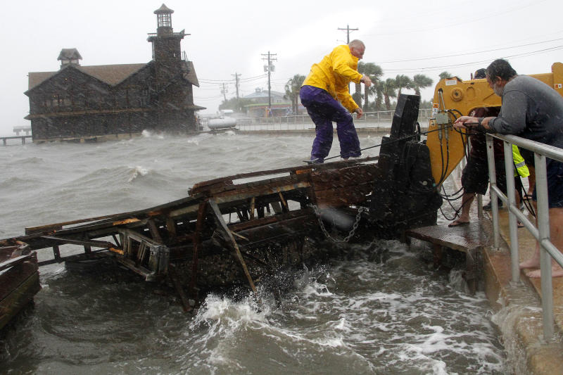 Cedar Key Fire Chief Robert Robinson walks on a section of a floating dock that broke loose during a storm surge from Tropical Storm Debby in Cedar Key, Fla., on Sunday, June 24, 2012. Tropical Storm Debby spun drenching rains Monday over northern Florida as it hung nearly stationary over the Gulf of Mexico, threatening to inundate low-lying neighborhoods. (AP Photo/The Gainesville Sun, Brad McClenny)