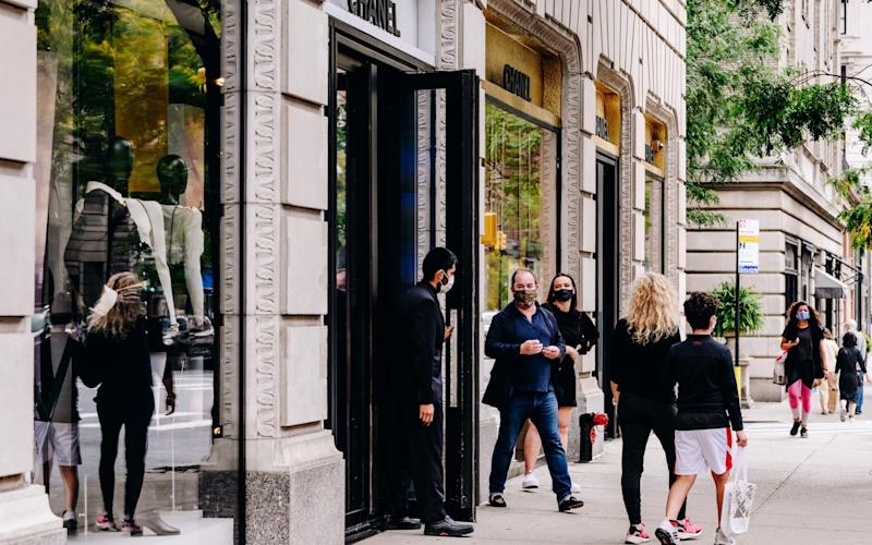 Pedestrians pass in front of the Chanel store on Madison Avenue in New York.  - Nina Westervelt/Bloomberg