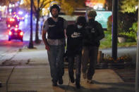 A man is detained by police during protests Friday, Oct. 9, 2020, in Wauwatosa, Wis. On Wednesday, District Attorney John Chisholm declined to charge Wauwatosa police Officer Joseph Mensah in the February fatal shooting of 17-year-old Alvin Cole outside a mall. (AP Photo/Morry Gash)