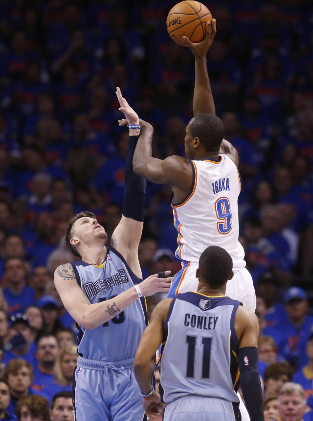 Oklahoma City Thunder forward Serge Ibaka (9) is fouled by Memphis Grizzlies forward Mike Miller (13) as he shoots in the first quarter of Game 7 of an opening-round NBA basketball playoff series in Oklahoma City, Saturday, May 3, 2014. (AP Photo/Sue Ogrocki)