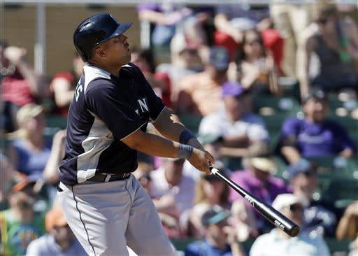 Seattle Mariners' Kendrys Morales watches his solo home run against the Colorado Rockies during the fifth inning of an exhibition spring training baseball game on Saturday, March 16, 2013, in Scottsdale, Ariz. (AP Photo/Marcio Jose Sanchez)