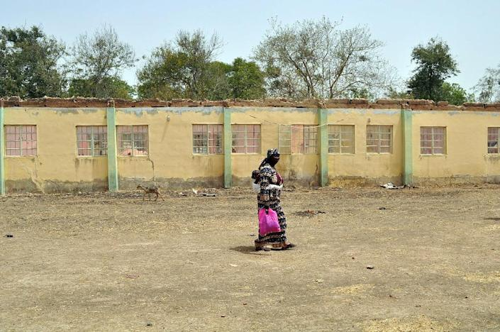 A mother of an abducted Chibok girl walks past the school hostel from where Boko Haram Islamists kidnapped 219 schoolgirls (AFP Photo/)