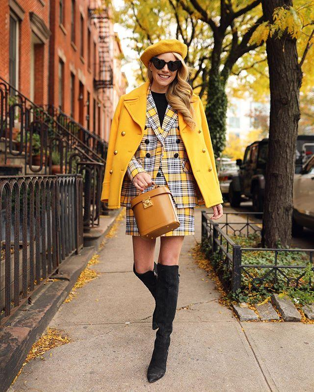 """<p>One of the keys to mastering fall style is learning the art of layering. It's easier said than done too: too many layers can look sloppy, but too few is pointless. The outfit pictured here consists of a matching mini skirt and blazer combination paired over a black shirt, with a yellow coat and black thigh high boots. </p><p><a href=""""https://www.instagram.com/p/BqQJAF8lCwL/"""">See the original post on Instagram</a></p>"""