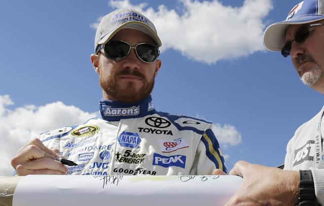 Driver Brian Vickers signs an autograph for a fan during practice for Sunday's NASCAR Sprint Cup Series auto race at Chicagoland Speedway in Joliet, Ill., Friday, Sept. 13, 2013. (AP Photo/Nam Y. Huh)
