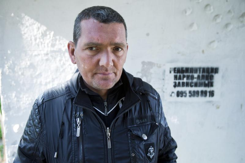 """In this photo taken Tuesday, April 1, 2014, Sergei, a patient of treatment for drug addiction, poses at a bus stop with an advert reading """"Rehabilitation of drug and alcohol addicts"""" in Sevastopol, Crimea. Across the Black Sea peninsula, some 800 heroin addicts and other needle-drug users take part in methadone programs, seen as an important part of efforts to curb HIV infections by taking the patients away from hypodermic needles that can spread the AIDS-causing virus. After Russia's annexation of Crimea methadone was banned. The ban could undermine years of efforts to reduce the spread of AIDS in Crimea. (AP Photo/Pavel Golovkin)"""