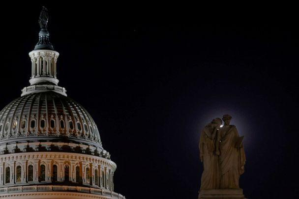 A pink Supermoon provides a halo behind the Peace Monument, with figures representing Grief and History, at the U.S. Capitol on April 26, 2021.   (Jonathan Ernst/Reuters)