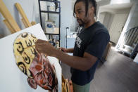 SMU defensive back RaSun Kazadi works on a painting at his apartment Wednesday, Aug. 11, 2021, in Dallas. A junior, Kazadi, who goes by the first name Ra, has been painting only since high school. Some works are lighthearted and fun. Some were done as stress relief. Others reflect a certain point in his life. He also runs a separate non-profit group to promote social justice and community conflict resolution. (AP Photo/LM Otero)