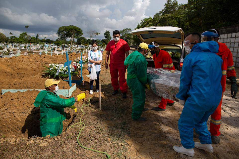 A burial takes place in a new area of the Nossa Senhora Aparecida cemetery reserved for COVID-19 victims, in Manaus, Brazil, on January 8, 2021 amid the novel coronavirus pandemic. (Photo by Michael DANTAS / AFP) (Photo by MICHAEL DANTAS/AFP via Getty Images)