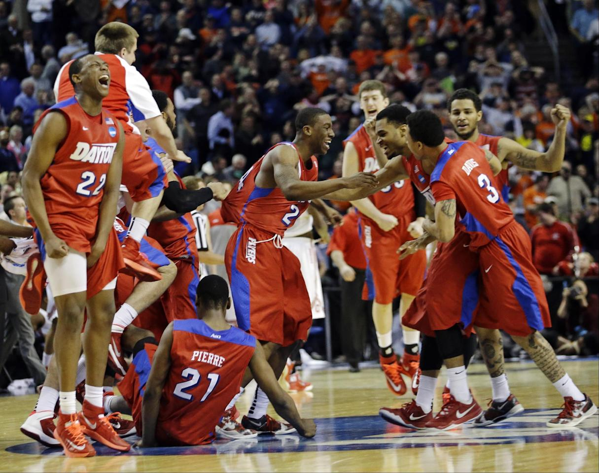 Dayton's Kendall Pollard (22) celebrates with teammates after they defeated Ohio State 60-59 in a second-round game in the NCAA college basketball tournament in Buffalo, N.Y., Thursday, March 20, 2014. (AP Photo/Frank Franklin II)