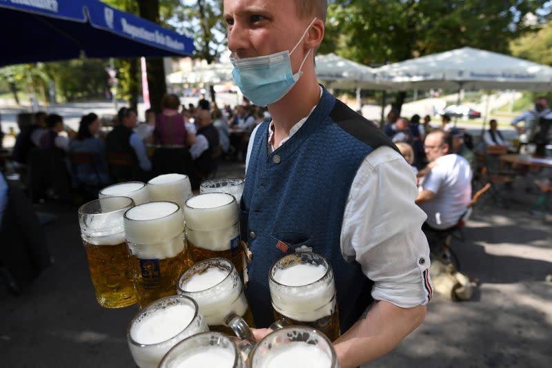 FILE PHOTO: Server carries mugs during the tapping of a barrel at a beer garden near Theresienwiese