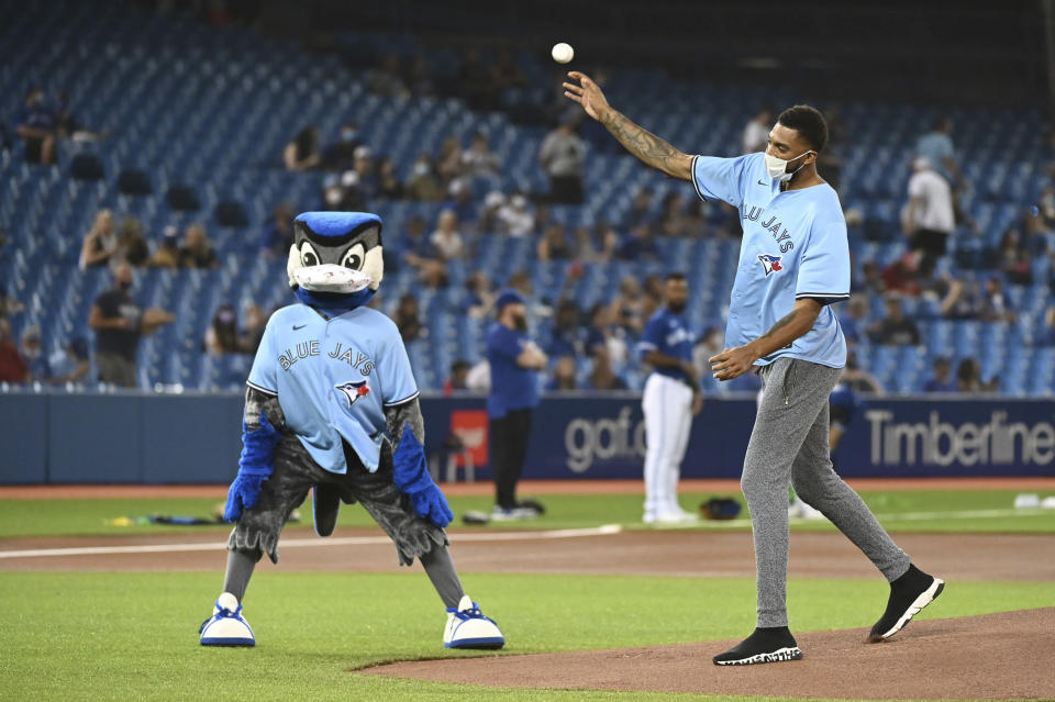 Toronto Raptors' Khem Birch, right, throws out the ceremonial first pitch before the first baseball game of a doubleheader between the Boston Red Sox and the Toronto Blue Jays in Toronto, Saturday Aug. 7, 2021. (Jon Blacker/The Canadian Press via AP)