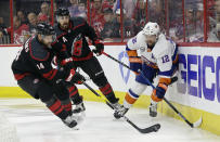 Carolina Hurricanes' Justin Williams (14) takes the puck from New York Islanders' Josh Bailey (12) while Hurricanes' Justin Faulk (27) looks on at rear during the first period of Game 4 of an NHL hockey second-round playoff series in Raleigh, N.C., Friday, May 3, 2019. (AP Photo/Gerry Broome)