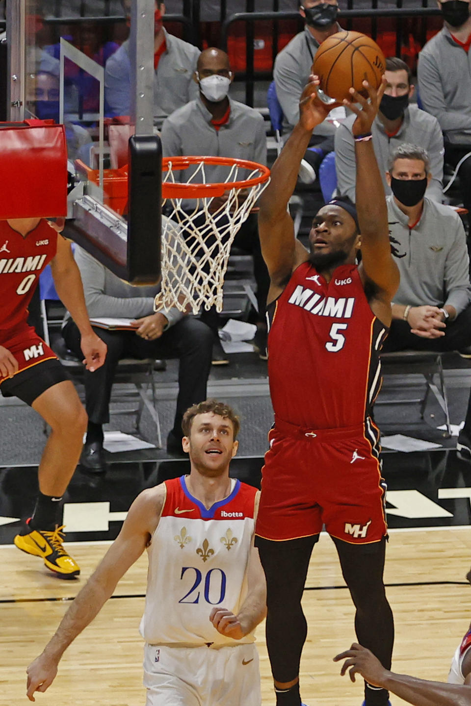 New Orleans Pelicans forward Nicolo Melli (20) looks up as Miami Heat forward Precious Achiuwa (5) goes to the basket during the second half of an NBA basketball game, Friday, Dec. 25, 2020, in Miami. (AP Photo/Joel Auerbach)