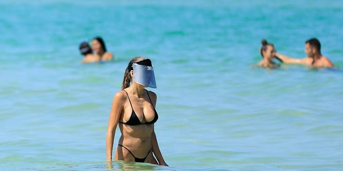 MIAMI BEACH, FLORIDA - JUNE 10: A woman wears a face shield as she wades in the ocean off South Beach on June 10, 2020 in Miami Beach, Florida. Miami-Dade county and the City of Miami opened their beaches today as the area eases restrictions put in place to contain COVID-19. (Photo by Cliff Hawkins/Getty Images)
